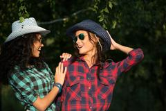 Two attractive girls in cowboy hats and sunglasses walking park. happily Stock Photos