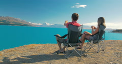 Young traveller couple sit at lake Pukaki in New Zealand relaxing Stock Footage