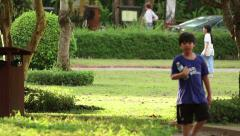 Children, adults, and jogger in park in Asia Stock Footage