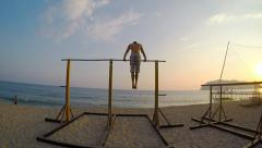 Man showing impressive strength, doing a Muscle Up in beach. - stock footage