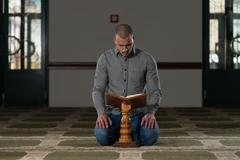 Muslim Man Reading Holy Islamic Book Koran - stock photo