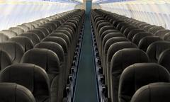 Airplane aisle with row of seats - stock photo