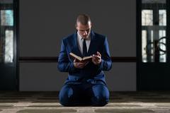 Muslim Businessman Reading Holy Islamic Book Koran - stock photo