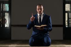 Muslim Businessman Is Reading The Koran Stock Photos