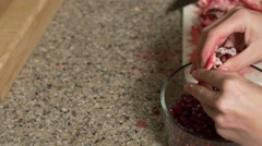 Pomegranate seeds being extracted into bowl- pan shot Stock Footage