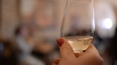 Hand Shaking A Glass Half-Filled With White Wine Stock Footage