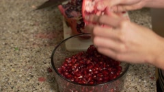 Stock Video Footage of woman breaking apart Pomegranate into bowl- close up