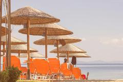 Sunshade and Chair On The Beach over blue summer sky. Stock Photos