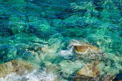 Coast with rocks on the beautiful turquoise Aegean Sea. Chalkidiki, Greece. Stock Photos