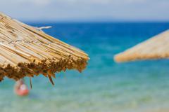 Stock Photo of Summer Travel Destination, closeup of sunshade over blue sea and sky.