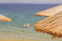 Summer Travel Destination, closeup of sunshade over blue sea and sky. - stock photo