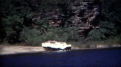 1954: Amphibious vehicle car boat going from land to water amongst rugged rocky - stock footage