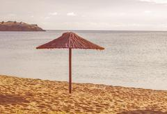 Sunshade on the empty sandy beach at sunset - stock photo