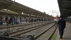 Train leaving while people are waiting on the train station platform, Bucharest Stock Footage