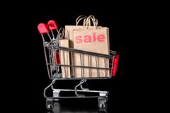 Closeup shopping cart with sale paper bags is isolated on black background Stock Photos