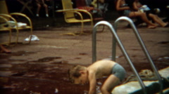 1956: Boy cautiously swims in public pool by himself for 1st time. - stock footage