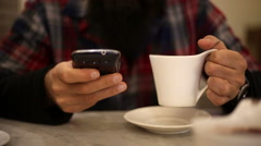 Man eating a cup of hot chocolate at bar and chatting with smartphone Stock Footage
