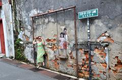 PENANG, MALAYSIA - NOV 26, 2015: Local tourist poses on Street Mural installa - stock photo