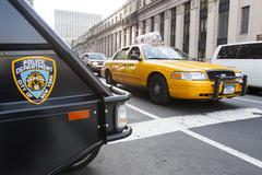 Yellow taxi and Nypd vehicle in Manhattan - stock photo