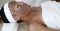 Woman with clay facial mask in beauty spa. Stock Footage