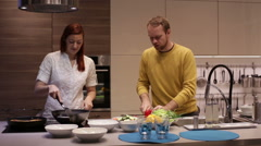 Young couple preparing food in kitchen. Stock Footage