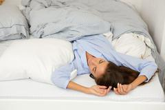 Young woman sleeping in comfortable bed Stock Photos