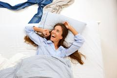 Portrait of a smiling woman awake in bed Stock Photos