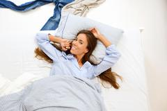Woman awake in bed and smiling - stock photo