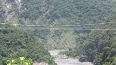 Bike pass through  suspension bridge in mountain valley Stock Footage