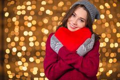 Lovely cute young woman hugging red heart over shiny background - stock photo