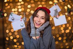 Lovely cheerful woman posing over handmade decoration and glittering backgrou Stock Photos