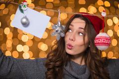 Thoughtful amusing young female using handmade christmas decoration over glit Stock Photos