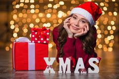 Beautiful woman lying near letters spelling word Xmas and  gifts - stock photo