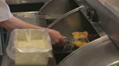 Battered fish being placed on hot plate - stock footage