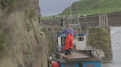 Fisherman preparing is small fishing boat in Crail harbour, Scotland Stock Footage
