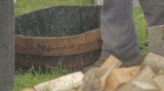 Man placing a barrel in the ground to make Arbroath smokies Stock Footage