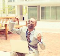 Happy successful young man with laptop computer celebrates success - stock photo