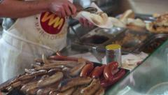 Big pile of fried sausages for hot dogs on the counter. Grilled sausages Stock Footage