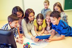 group of kids with teacher and tablet pc at school - stock photo