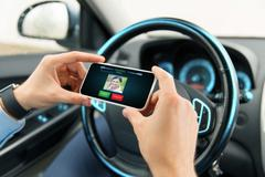 Male hands with video call on smartphone in car Stock Photos