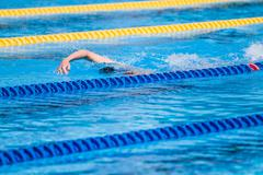 Swimmers Warming-up in the morning and doing a few Pool distances - stock photo