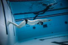 Dynamic no Fins Freediver doing a Turn during Performance from Underwater - stock photo