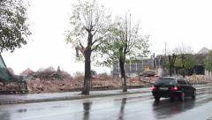 Machinery working on the demolition of buildings near a frequented road 07 Stock Footage