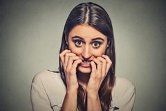 young anxious unsure hesitant nervous woman biting her fingernails - stock photo