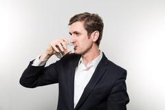 studio shot of businessman with a glas of sparkling water - stock photo