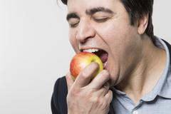 studio shot of happy person eating an apple - stock photo