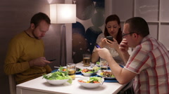 Friends looking on smartphone during dinner Stock Footage