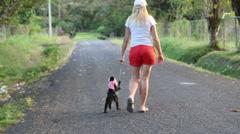 Blonde Woman in Shorts Walking Her Monkey - stock footage