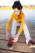 Girl fastens laces on gym shoes on bridge at river. - stock photo