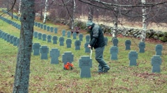 Disabled veteran with crutches near to the tomb monument with flowers Stock Footage